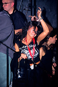 A girl in motorhead t-shirt dancing at rock gig, UK 2000's