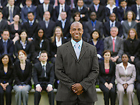 Business man standing in front of business people sitting in bleachers portrait