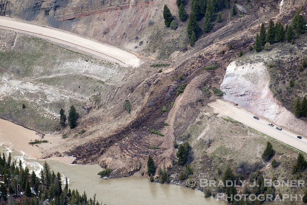 A massive landslide covers about 300 feet of Highway 89 in Snake River Canyon between the towns of Alpine and Jackson, Wyo. The slide, which is about 40 feet deep on the road and almost 2,000 feet long, began as a small mudslide but more than tripled in size by the next day. Crews examining the slide can be seen as orange dots on the right side of the mass.