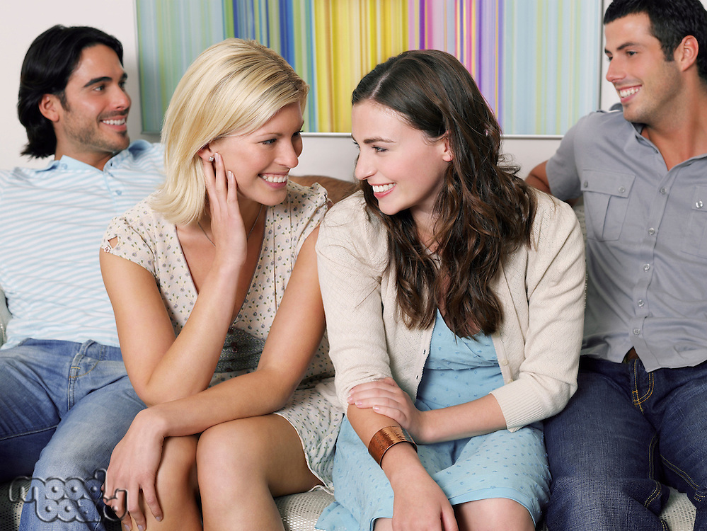 Group of young people sitting in row on sofa