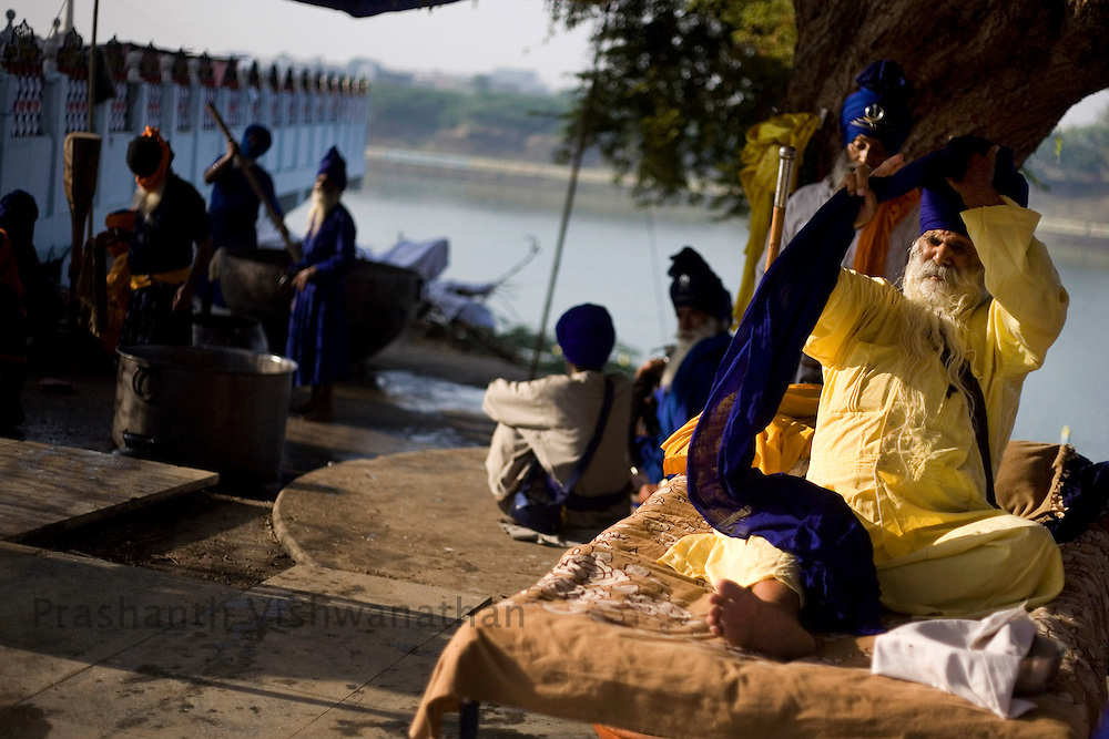 A warrior Sikh, or Nihang, ties his turban at a camp in Nanded, some 650 kms south of Mumbai on November 1, 2008. Sikhs all over the world are celebrating the 300th anniversary of the consecration of their holy book and perpetual Guru, the Guru Granth Sahib.