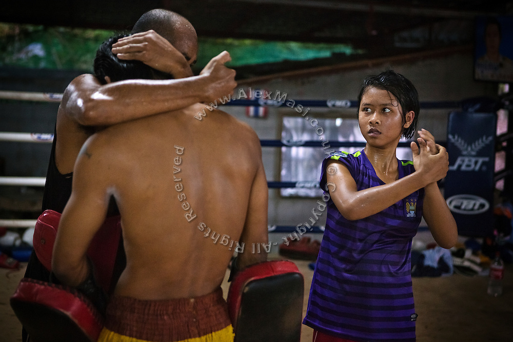 Phatsorn Bunmasen, 14, is learning the hands position for clutching, as shown by her instructor Wichai Saengkeaw, 42, at the gym where she practises Muay Thai boxing, in a village near Ubon Ratchathani, northeast Thailand.
