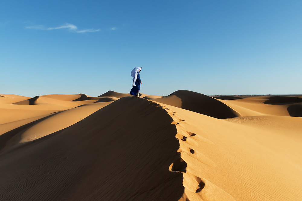Traditional dressed Moroccan man with turban stands on a sand dune in the Sahara desert.