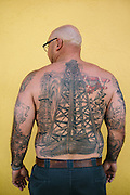 "Scott Mathis, 38, an oil well site manager, wears his heritage on his skin with two oil derricks and a crop duster tattooed to his back. Mathis is a fourth generation oil field worker. His grandfathers and a great-grandfather were all oil drilling hands. ""I was born with like 10 years experience,"" Mathis said."