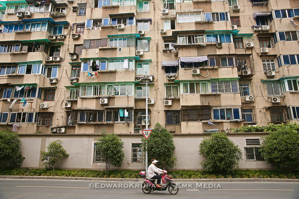 Woman riding an electric bike by an apartment building in Hangzhou, China.