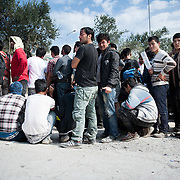 Afghan men queuing to be registered and receive a temporary document that allows them to travel to mainland Greece at Moria camp, Lesvos, Greece. Usually women and children wait at the tents while men are waiting under the sun to receive their documents.