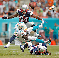 Miami Dolphins running back Lamar Miller (26) fumbles and loses his shoe after getting hit by the Patriots Logan Ryan in the second quarter as the Miami Dolphins host the New England Patriots at Sun Life Stadium in Miami Gardens on Sunday, September 7, 2014.