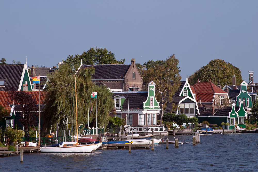 Tiny and colorful fishermen's cottages line the Zaan River at Zaanse Schans, an open-air historical museum near Amsterdam.