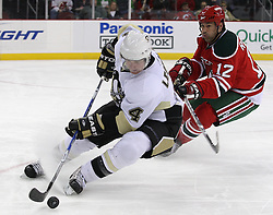 Mar 17, 2010; Newark, NJ, USA; Pittsburgh Penguins defenseman Jordan Leopold (4) skates with the puck away from New Jersey Devils right wing Brian Rolston (12) during the second period at the Prudential Center.