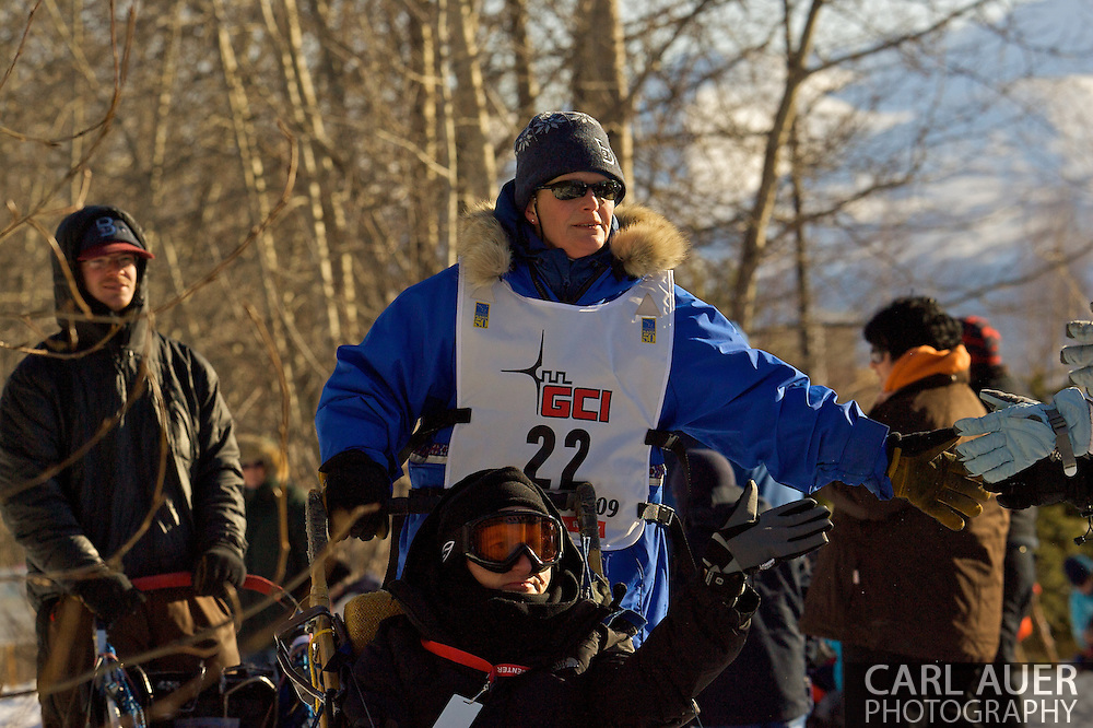 March 7th, 2009:  Anchorage, Alaska - Judy Currier of Fairbanks, Alaska greats fans along the route coming off of Behm Lake near the Alaska Native Hospital during the Ceremonial Start of the 2009 Iditarod.