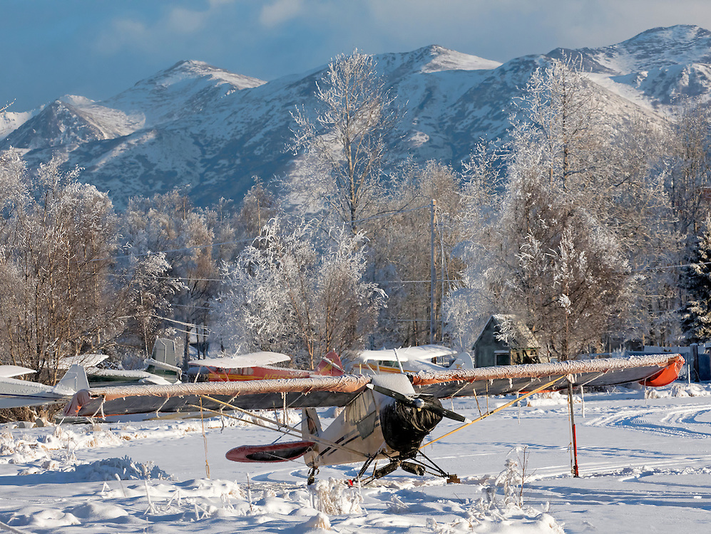 Alaska; Scenic view of Supercub PA-18 parked for the winter on frozen Lake Hood, Anchorage with Chugach Mountain in background.