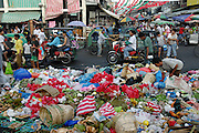 "Outside the Quiapo Market in the Philippines, people pick through the trash discarded from the early-morning wholesale market. Inside, the covered market is a tumult of activity and offers an extraordinary variety of goods, ranging from food, clothing, consumer electronics, and patent medicines to religious images and even prayers (busy people can outsource their prayers to the Quiapo Church's ""prayer ladies""). Hungry Planet: What the World Eats (p. 239). This image is featured alongside the Cabaña family images in Hungry Planet: What the World Eats."