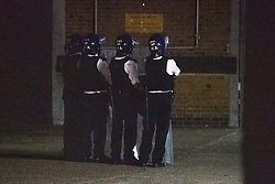 "© Licensed to London News Pictures. 21/07/2020. London, UK. Police wearing helmets and holding long riot shields stand and look on at the scene at the rear of the Southall Fire Station. A large scale emergency services operation underway while police are in a standoff with a person ""at height"" close to the Southall Fire station. Photo credit: Peter Manning/LNP"