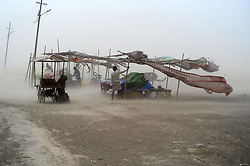 June 16, 2017 - Allahabad, Uttar Pradesh, India - Vendors hold their makeshift shelter during a dust storm at the Sangam, the confluence of the Ganges, Yamuna and mythical Saraswati rivers in Allahabad. (Credit Image: © Prabhat Kumar Verma via ZUMA Wire)