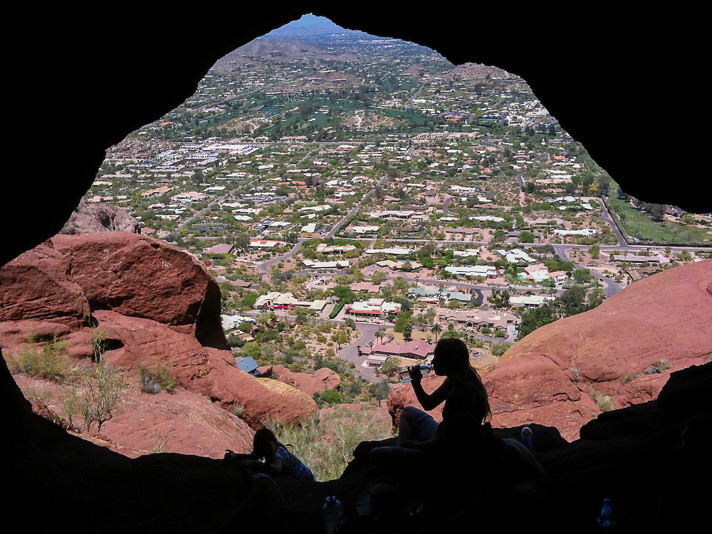 A thirsty hiker takes a break in the shade provided by one of Camelback Mountain's many caves.