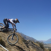Leighton Kirk from Karitane in action during the New Zealand South Island Downhill Cup Mountain Bike series held on The Remarkables face with a stunning backdrop of the Wakatipu Basin. 150 riders took part in the two day event. Queenstown, Otago, New Zealand. 9th January 2012. Photo Tim Clayton