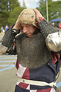 Garden City, New York, U.S. - June 14, 2014 - DAVID OLSEN, of Peeksville NY, is a USA Knights member putting on cloth protective cap for under his helmet, is wearing warrior combat sport armor at Eternal Con, the annual Pop Culture Expo, with costumes, Gaming, Sci-Fi, Cosplay, Horror, and held at the Cradle of Aviation Museum on Long Island. Armored Combat League members compete in international medieval combat competitions.