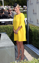 A pregnant Zara Phillips waits to present the trophy to the winning jockey in the main race during  Ladies Day at Glorious Goodwood in the UK  Thursday, 1st August 2013<br />