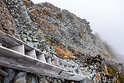 "Seen here in the fog, the infamous Daikiretto Gap, secured by chains and ladders, is one of the most difficult non-technical routes in Japan. Kita-hotaka Mountain Hut perches near the summit of Mount Kitahotaka, which reaches 3106 m elevation (10,190 ft, Japan's 9th highest) in Chubu-Sangaku National Park, Japan. This is the highest hut in Japan, excluding those on Mt Fuji. I hiked Kitahotaka (or Kitahotaka-dake) 4km round trip from Karasawa Goya hut via a steep trail secured with chains & ladders ascending 800 meters. Mt Kitahotaka is the second highest peak on Mount Hotaka (Hotaka-dake or the Hotaka Mountains), which are in the ""Northern Japan Alps"" (Hida Mountains). North of Kitahotaka-dake lies an exposed 3.5+ hour scramble via Daikiretto Gap helped by chains and ladders, connecting with Minamidake Mountain Hut. I avoided the Daikiretto by returning to Karasawa cirque, then walking all the way back to a comfortable dorm slot reserved at Tokusawa-en backcountry lodge (16 km, 800 meters up, 1615 m down)."