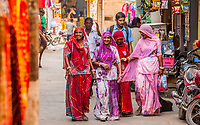 Four women walking down a street in Jaisalmer, Rajasthan, India in their colorful clothing.