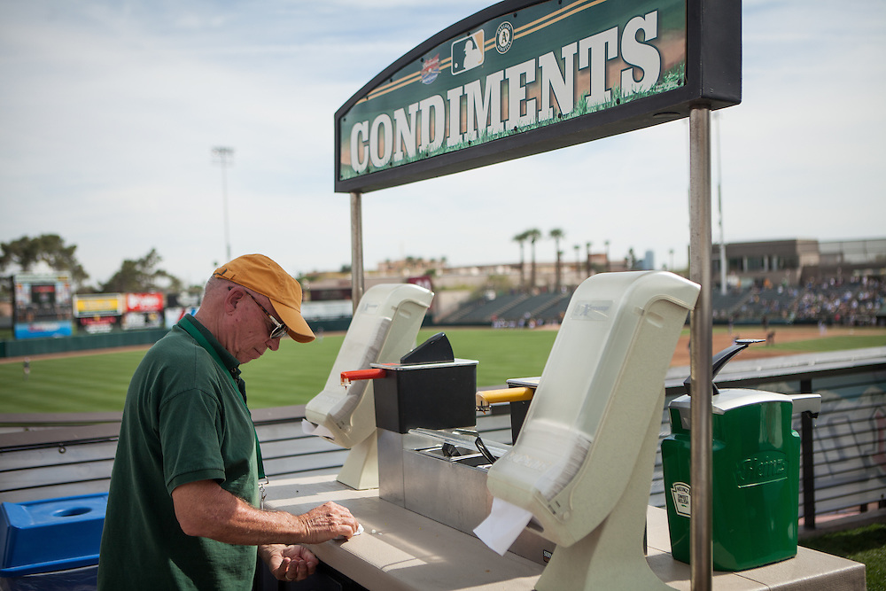 Chuck Stout, former head of product development for McDonald's, wipes off a condiments stand at spring training in Tempe, Arizona.
