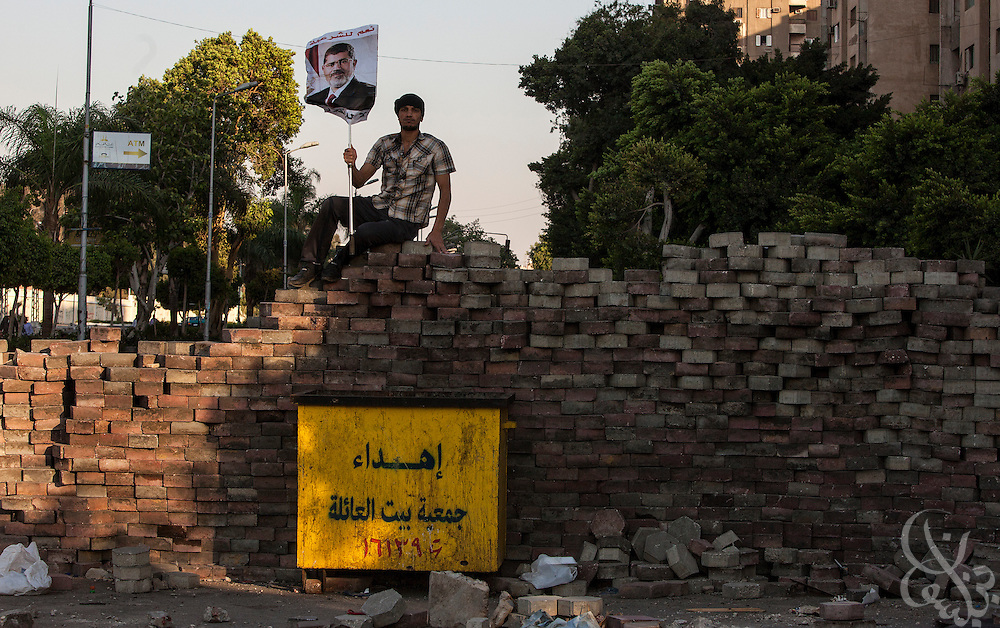 A supporter of deposed Egyptian president Mohamed Morsi protests atop a brick wall guarding the edge of the now month long demonstrations and sit-in around the Rabaah al-Adawia mosque and square in the Nasr City district of Cairo Friday July 26, 2013.  The supporters are demanding the reinstatement of the deposed President and are opposed to the Egyptian military, which they say has undertaken an undemocratic coup.