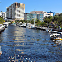 New River Flowing in Downtown Fort Lauderdale, Florida<br /> The New River, which begins in the Everglades, flows through downtown Fort Lauderdale before reaching the Atlantic Ocean near Port Everglades.  The Seminole Indians first gave it the name of &ldquo;Himmarshee&rdquo; which means &ldquo;new water.&rdquo;  Today it is an active waterway for yachts and pleasure boats.  On the left is part of the promenade called Riverwalk.