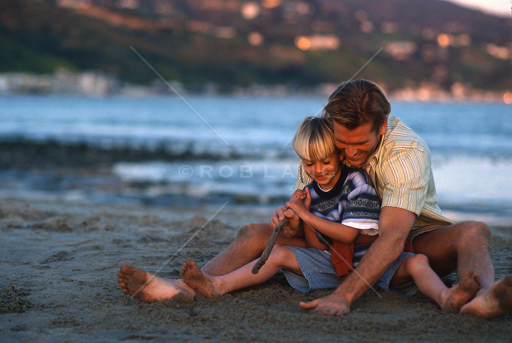 man and young boy drawing in the sand at the beach in Malibu, CA