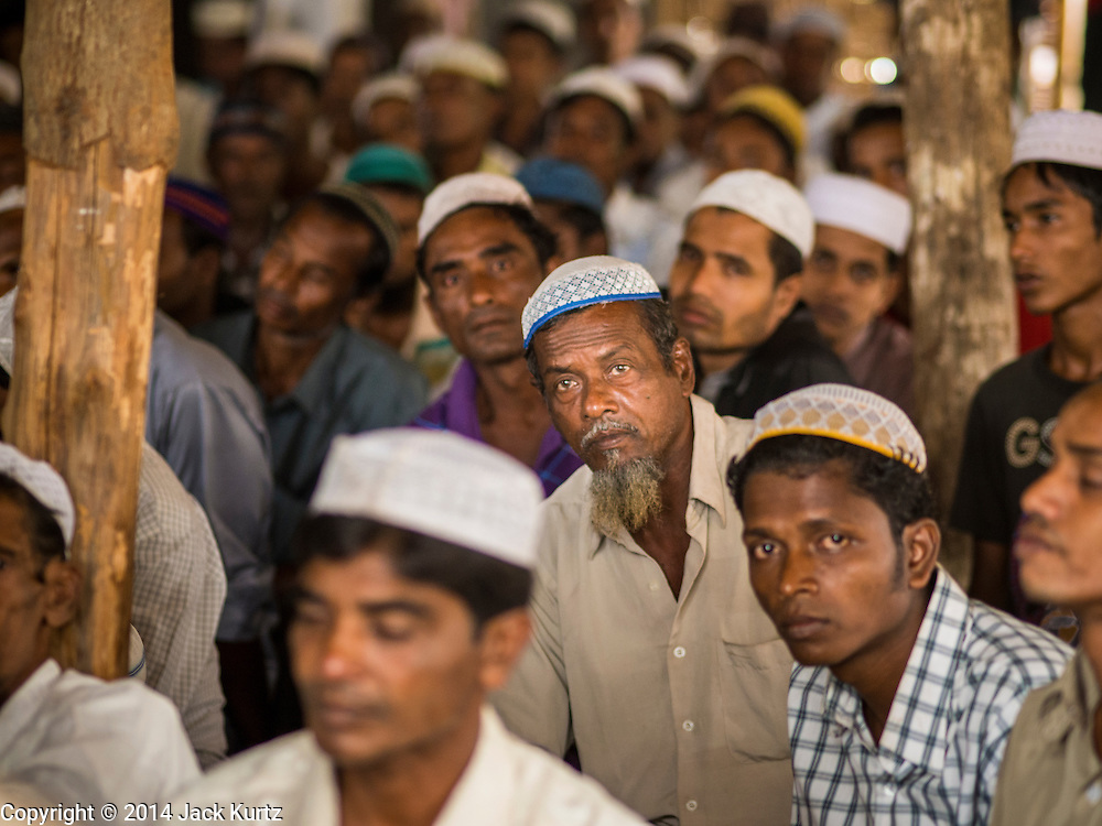 07 NOVEMBER 2014 - SITTWE, RAKHINE, MYANMAR: A Rohingya Muslim men at Friday prayers in their mosque in an IDP camp for the Rohingya. The mosque is a temporary building made out of palm fronds. After sectarian violence devastated Rohingya communities and left hundreds of Rohingya dead in 2012, the government of Myanmar forced more than 140,000 Rohingya Muslims who used to live in and around Sittwe, Myanmar, into squalid Internal Displaced Persons camps. The government says the Rohingya are not Burmese citizens, that they are illegal immigrants from Bangladesh. The Bangladesh government says the Rohingya are Burmese and the Rohingya insist that they have lived in Burma for generations. The camps are about 20 minutes from Sittwe but the Rohingya who live in the camps are not allowed to leave without government permission. They are not allowed to work outside the camps, they are not allowed to go to Sittwe to use the hospital, go to school or do business. The camps have no electricity. Water is delivered through community wells. There are small schools funded by NOGs in the camps and a few private clinics but medical care is costly and not reliable.   PHOTO BY JACK KURTZ