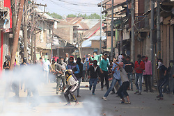 April 28, 2017 - Srinagar, Jammu and Kashmir, India - Amid the tear gas smoke Kashmiri protesters throw stones at government forces during a protest after Friday prayers in Sopore. (Credit Image: © Mohammad Abu Bakar/Pacific Press via ZUMA Wire)