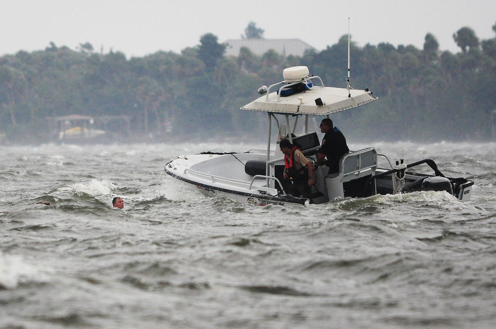 Andrew Knapp, FLORIDA TODAY -- Aug. 27, 2011 -- Officers from the Melbourne Police Department and the Florida Fish and Wildlife Conservation Commission rescue three people who fell off their sailboat Saturday and into the Indian River during a wind storm just north of the Eau Gallie Causeway near Melbourne.