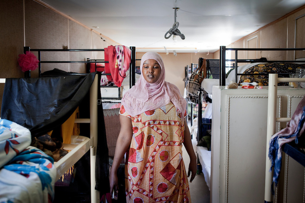 HAL FAR, MALTA - JUNE 21: Fatima Aden, 26, is an immigrant from Somala who lives in a container with 13 other single women at the Tent Village, an open centre in Hal Far (which translates as &quot;Rat's Town&quot;) on June 21, 2011. Fatima Aden arrived in Malta on March 28th after fleeing the unrest in Libya. She left from the port of Az Zawiyah, 50 miles from tripoli. There were two boats, and 180 peple were on hers. It took them 33 hours to reach Malta. Fatima lived in Libya for one year and 9 months and worked as a chemist for 500 dinars, which were enough for her. She didn't want to leave but she was forced to. She wasn't threatened and didn't have to pay for the boats. The boats were given to the people by government officials. She's been in Malta now for 3 months and obtained subsidiary protection. She left Somali in 2006 when she was 21 and went first to Nairobi, Kenya, then South Africa. She has 2 sons living with her mother in Uganda. She's not married. Fatima lives in a container in the Hal Far Tent Village with 13 other single women: 2 Ethiopians, 2 Eritreans, 1 Nigerian, 9 Somalis. The majority of migrants living in the tent village is from Somalia. No lights, though they have electricity for a mini fridge. Fatima has a sister in Sweden. <br /> <br /> The Open Centres in Malta serve as a temporary accomodation facility, but they ended becoming permanent accomodation centres, except for those immigrants who receive subsidiary protection or refugee status and that are sent to countries such as the United States, Germany, Poland, and others. All immigrants who enter in Malta illegally are detained. Upon arrival to Malta, irregular migrants and asylum seekers are sent to one of three dedicated immigration detention facilities. Once apprehended by the authorities, immigrants remain in detention even after they apply for refugee status. detention lasts as long as it takes for asylum claims to be determined. This usually takes months; asylum seekers often wait 