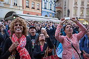 Tourists watch and photograph the procession of the apostles at the astronomical clock at Old Town Square.