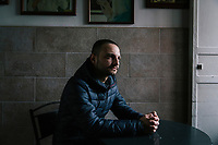 "TARANTO, ITALY - 22 FEBRUARY 2018: Luca Greco, an unemployed 30-years old living with his parents in Tamburi, the working-class district adjacent the ILVA steel mill, poses for a portrait at the Mini Bar in Taranto, Italy, on February 22nd 2018.<br /> <br /> Luca Greco has worked occasionally in call centers for a minimum salary, but hasn't had a job since 2013. His 65 years-old father is unemployed  since 2003 and his mother works as a care-giver. He lives with his parents and 13 years-old brother. ""I  absolutely don't see a future in Taranto or in Italy. If I leave Tamburi, I will leave the country. I see a dark, tragic future"". When asked who he will vote in the upcoming Italian General Elections, Luca said: ""You could still make a distinction between the political parties in the 1960's. They're all the same. The Five Stars Movement is the new thing. One could vote them to give them a chance. But I won't"".<br /> <br /> Taranto, a  formerly lovely town on the Ionian Sea has for the last several decades been dominated by the ILVA steel mill, the largest steel plant in Europe. It was built by the government in the 1960s as a means of delivering jobs to the economically depressed south, but has been implicated for a cancer as dioxin and mercury have seeped into local groundwater, tainting the food supply, while poisoning the bay and its once-lucrative mussels."