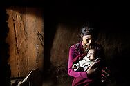 A sixteen-year-old girl who preferred not to be named holds her three-month-old baby boy in her family's chaupadi shelter, a squat crawlspace under the home where the women of the household sleep during their periods, Achham, Nepal, December 9, 2012. She became pregnant when she was raped by a neighbor and family acquaintance while sleeping alone in the shelter. She is trying to track down the rapist, who fled the country, in order to give him the baby, who she cannot afford to care for.<br />