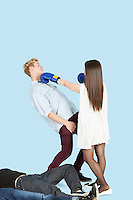 Female boxer punching man with people lying in foreground