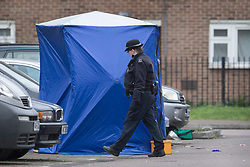 © Licensed to London News Pictures. 20/03/2017. London, UK. A police officer passes a tent covering the scene of a fatal shooting in Barking, east London, where an 18 year old man was shot in the head on Sunday evening. Photo credit: Peter Macdiarmid/LNP