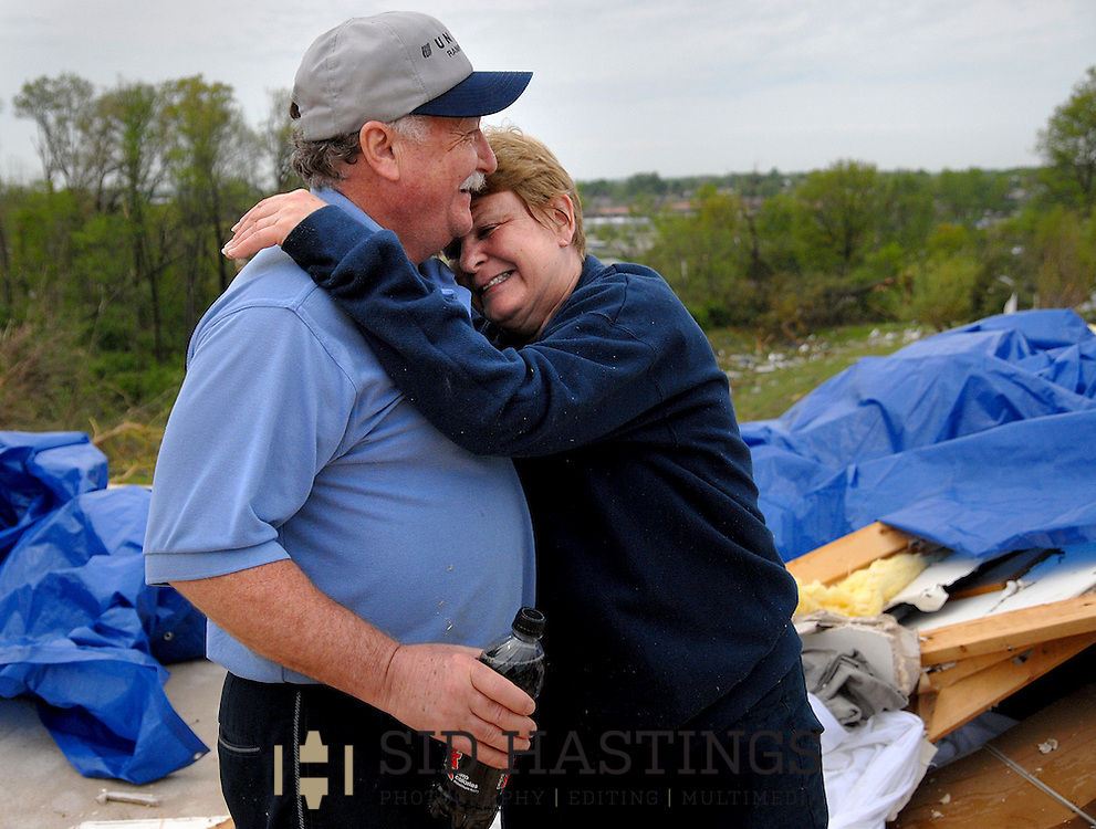 23 APRIL 2011 -- BRIDGETON, Mo. -- Terry Hayes (left) and his wife Mary Ellen Norton-Hayes embrace as family, friends, neighbors and volunteers help collect salvaged items from their home on Beaverton Drive in Bridgeton, Mo. Saturday, April 23, 2011. The home was destroyed in an apparent tornado that struck the community Friday, April 22, 2011. Image © copyright 2011 Sid Hastings.