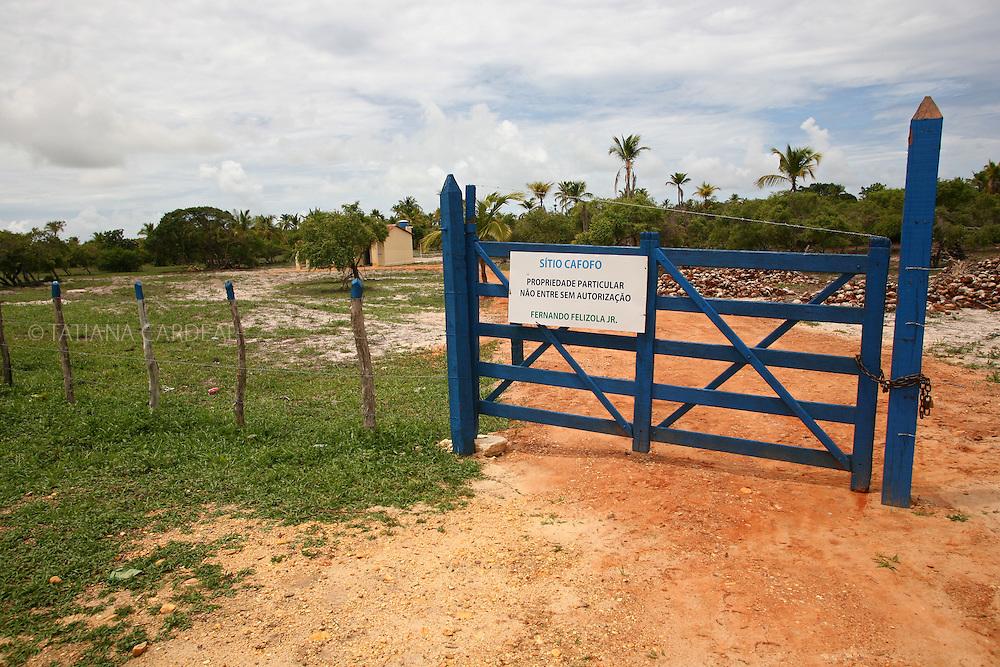 Entrada da propriedade de particular, cercada recentemente para impedir a colheita livre de mangaba..Ao fundo, a casa nova para os vigilantes da fazenda.