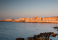 Old buildings along the seafront in Ortigia at sunrise, Syracuse, Sicily, Italy
