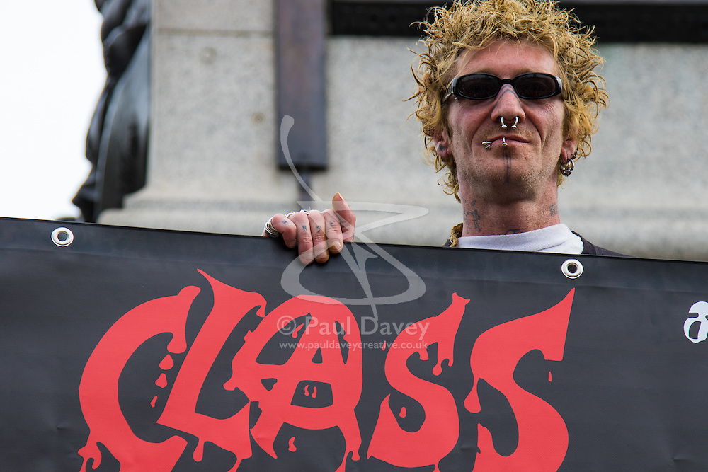 London, May 27th 2015. An anarchist from the group Class War peers over his banner at Nelson's Column in Trafalgar Square.