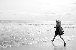 girl walking towards the ocean in a dress