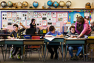 Fourth-grade teacher Brenda Bennett, right, helps Ethan Howe, 9, with a cursive writing assignment while Braden Martin, 10, raises his hand with a question and Rose Novotny, 9, completes a packet of cursive writing worksheets at Thetford Elementary School in Thetford, Vt., January 24, 2014.(Valley News - Will Parson)