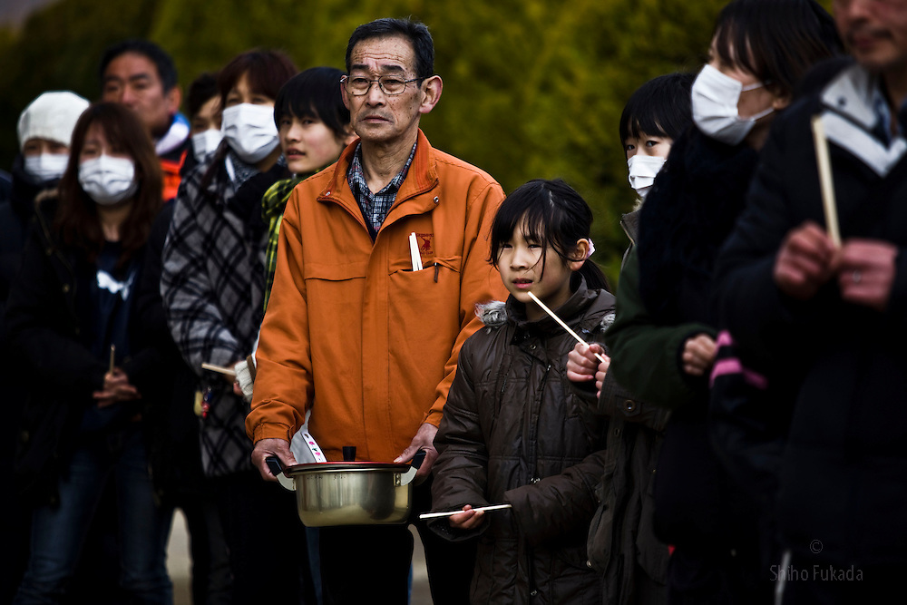 Evacuees wait for charity meal at temporary shelter in Kesennuma in Miyagi, Japan, March 17, 2011.