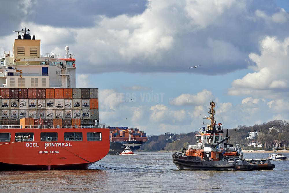 """Das Containerschiff """"OOCL Montreal"""" am Athabaska-Kai. Der Schlepper """"Bugsier 10"""" bereitet das Auslaufen vor, während das Cargo-Schiff """"APL Chongqing"""" in den Hafen einläuft."""