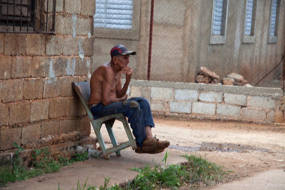Central America, Cuba, Remedios. Cuban man leans back in chair on corner.