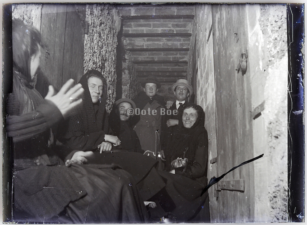 people sitting in a corridor of tenant housing 1900s