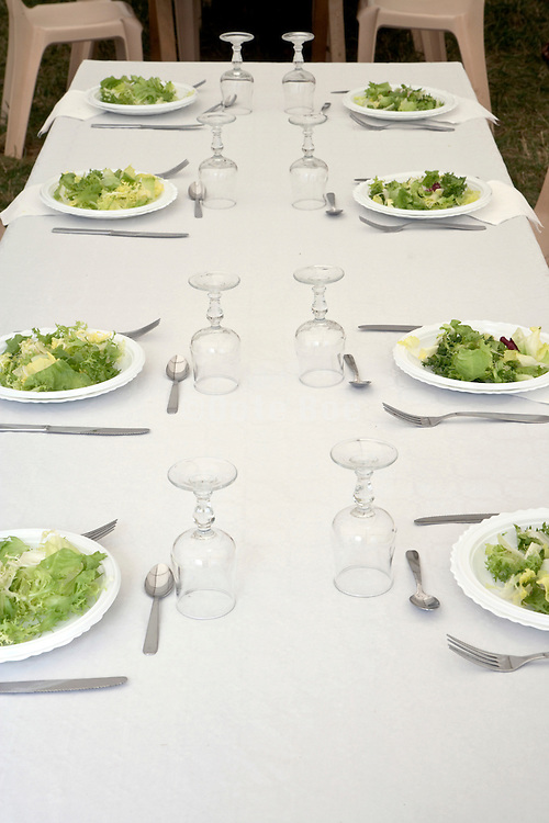 table with plates and utensils with green salad