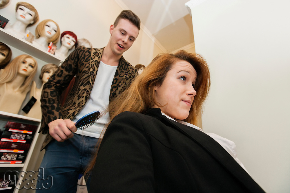 Male hairstylist brushing female customer's hair in salon