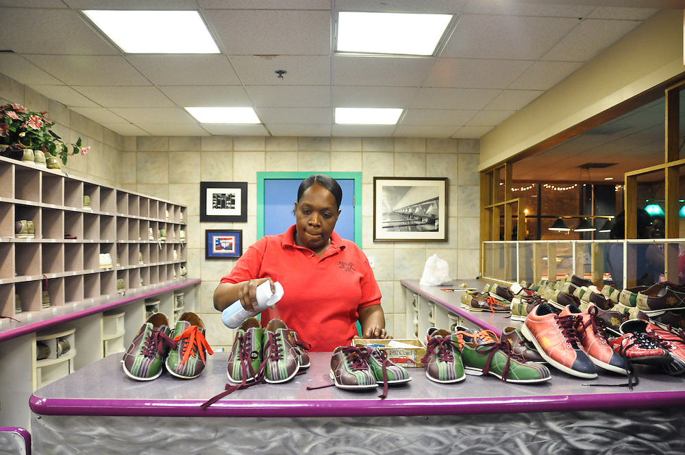A bowling alley employee at Waveland Bowl on Western Ave sprays disinfectant into recently-returned bowling shoes. Chicago, 2011
